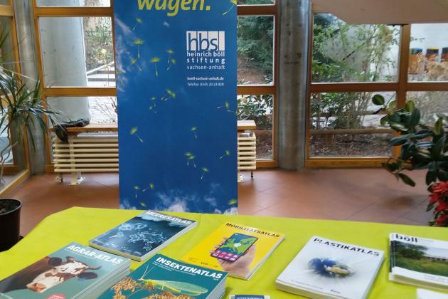 Tisch mit verschiedenen Publikationen, Banner der Stiftung im Hintergrund